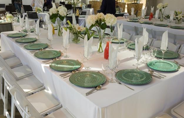 Grande mesa e cadeiras brancas para a recepção do evento da cerimônia dentro de um restaurante requintado e pessoas