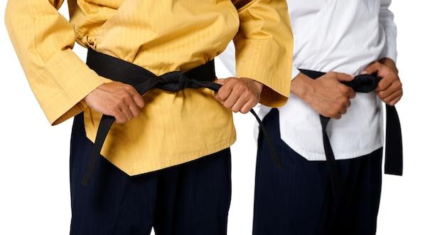 Grande mestre faixa preta taekwondo professor segurando e amarrar a pose do cinto, estúdio com parte da cintura sobre fundo branco isolado