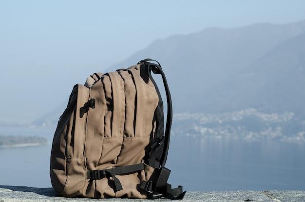 Grande mochila de caminhada com montanhas desfocadas ao fundo