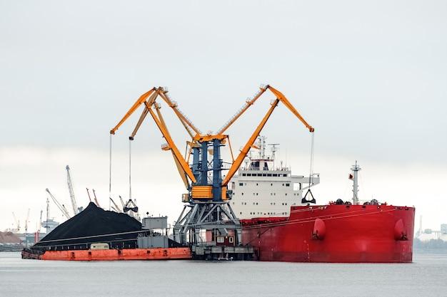 Grande navio de carga vermelho carregando carvão no porto