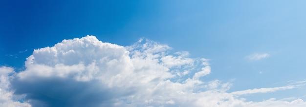 Grande nuvem branca à luz do sol no céu azul, panorama