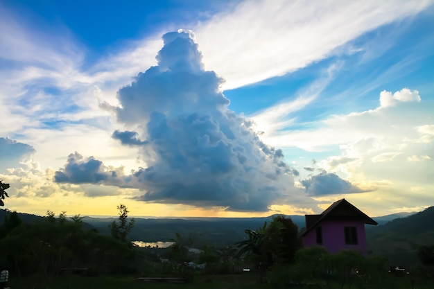 Grande nuvem branca com chuva cai no reservatório tem uma casa-de-rosa na montanha e blu