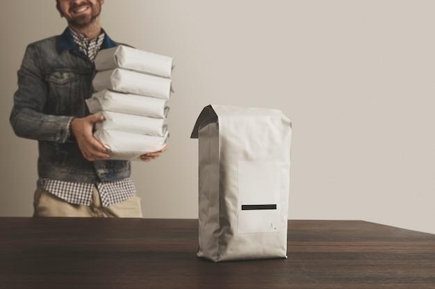 Grande pacote lacrado volumoso em branco com produto isolado na mesa de madeira na frente de um sorriso fora de foco