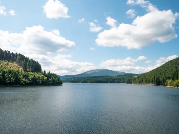Grande paisagem da romênia com montanhas, lago, árvores e nuvens em um dia ensolarado de verão