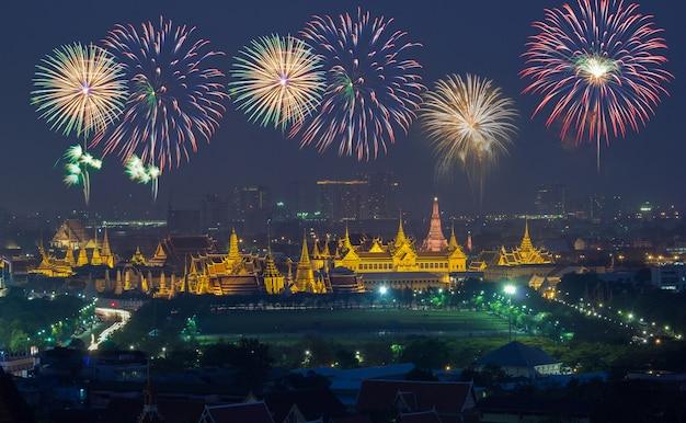 Grande palácio no crepúsculo com fogos de artifício coloridos (bangkok, tailândia)