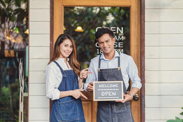 Grande parceiro asiático proprietário de pequena empresa com as mãos segurando e mostrando o quadro-negro