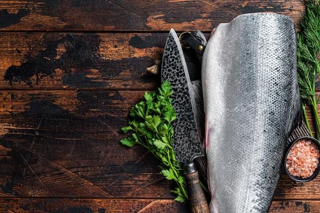 Grande pedaço de peixe salmão cortado cru em uma tábua de madeira com faca do chef. fundo de madeira escuro. vista do topo. copie o espaço.