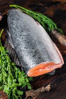 Grande pedaço de peixe salmão cortado cru em uma tábua de madeira com faca do chef. fundo de madeira escuro. vista do topo.