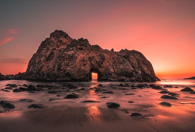 Grande penhasco na praia pfeiffer, nos eua, durante o pôr do sol