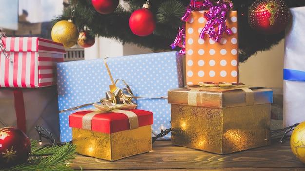Grande pilha de caixas de presente coloridas e bugigangas caídas no chão sob a árvore de natal