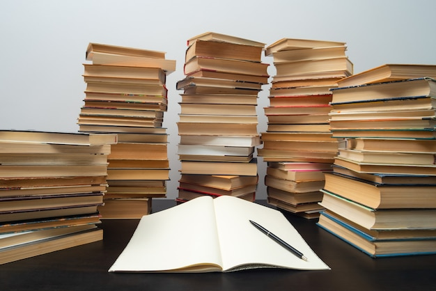 Grande pilha de livros sobre a mesa - estudando antes do exame.