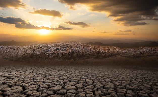 Grande pilha de lixo da montanha e poluição ao sol está se pondo em solo rachado em áreas áridas