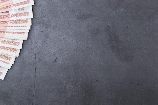 Grande pilha de notas de dinheiro russo de cinco mil rublos deitado fã no cimento cinza
