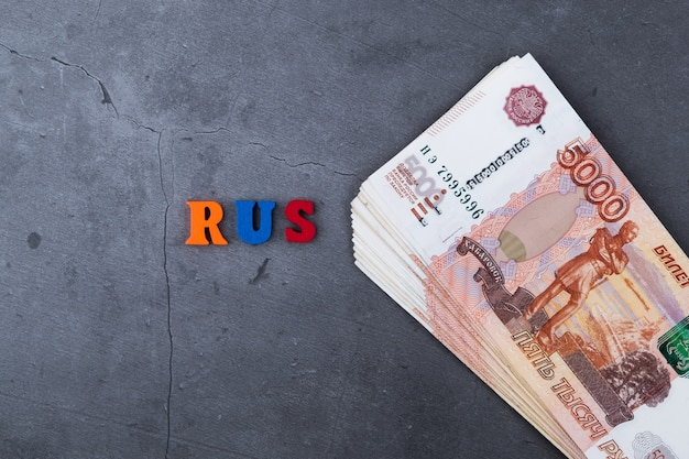 Grande pilha de notas de dinheiro russo de cinco mil rublos deitado no fundo cinza