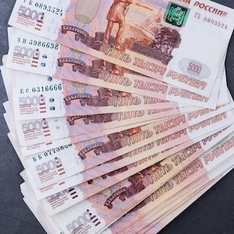 Grande pilha de notas de dinheiro russo de cinco mil rublos mentindo fã sobre um fundo cinza de cimento.