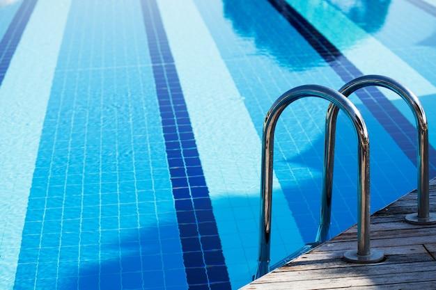 Grande piscina azul ao ar livre no local com escadas para descer na água
