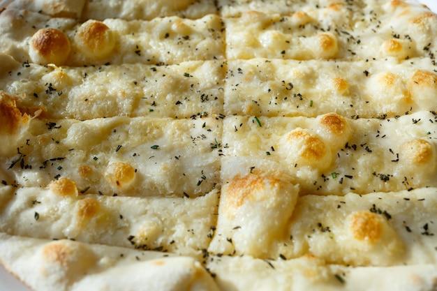 Grande pizza acabada de fazer com especiarias polvilhadas com queijo à luz do sol.