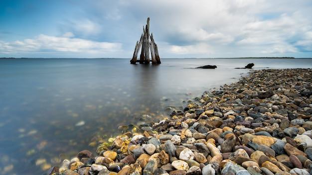 Grande plano de ângulo alto de pedras à beira-mar com o mar