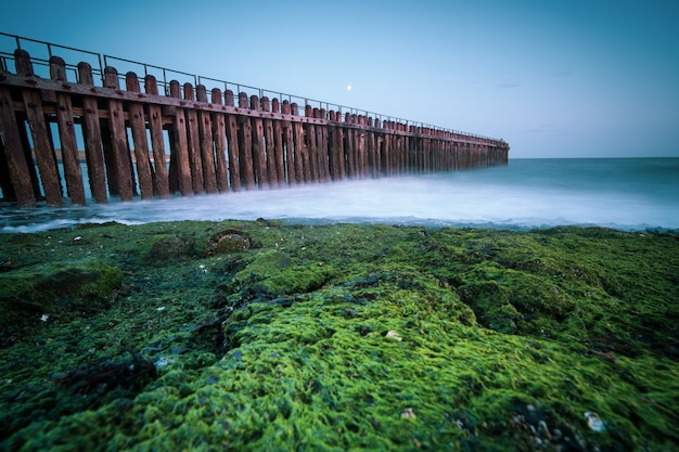 Grande plano de ângulo alto de uma cerca de madeira à beira-mar em direção ao mar