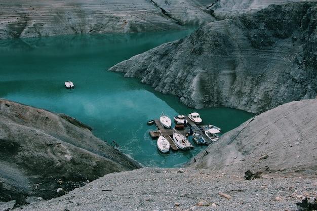 Grande plano de barcos no corpo de água, rodeado por montanhas