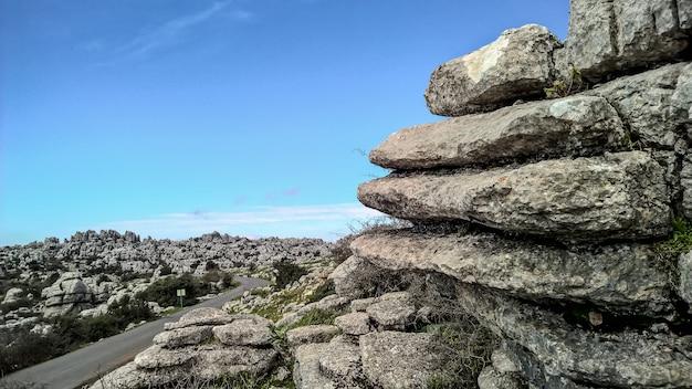 Grande plano de camadas de rochas e um céu claro e brilhante ao longo de uma estrada de asfalto liso