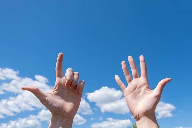 Grande plano de gesto da mão de uma mulher mostrando uma palma aberta e dois dedos isolados em um fundo de céu azul com nuvens, o número sete é o símbolo da linguagem de sinais