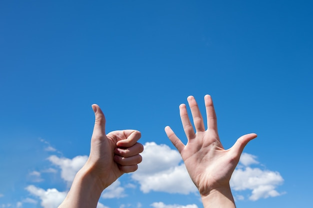 Grande plano de gesto de uma mão de mulher mostrando uma palma aberta e o polegar isolado em um fundo de céu azul com nuvens, linguagem de sinais, símbolo número seis