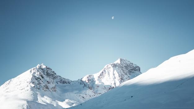 Grande plano de montanhas cobertas de neve sob um céu azul claro com meia-lua