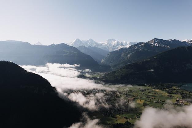Grande plano de montanhas e colinas, rodeado de prados verdes e nevoeiro