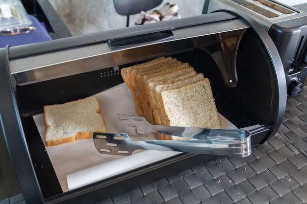 Grande plano de pão na caixa de pão de aço moderno
