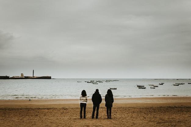 Grande plano de três pessoas em pé perto da beira-mar com pequenos barcos flutuando no mar