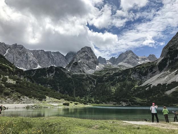 Grande plano de turistas perto de um lago no fundo das montanhas, rodeado de árvores e plantas verdes