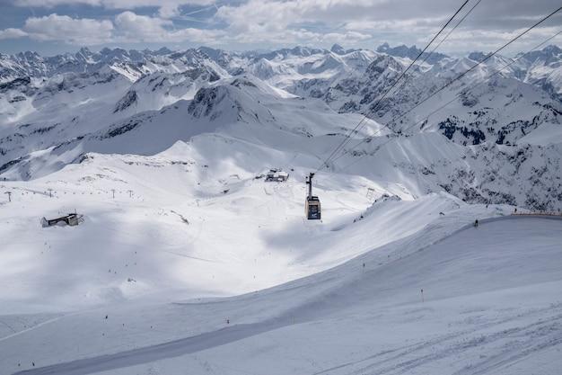 Grande plano de um carrinho de cabo em uma montanha nevada