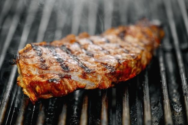 Grande plano de um delicioso bife na grelha em chamas