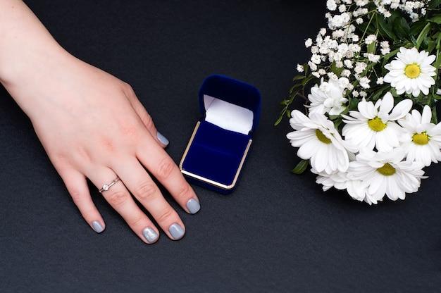 Grande plano de um elegante anel de diamante no dedo com flores e uma caixa azul