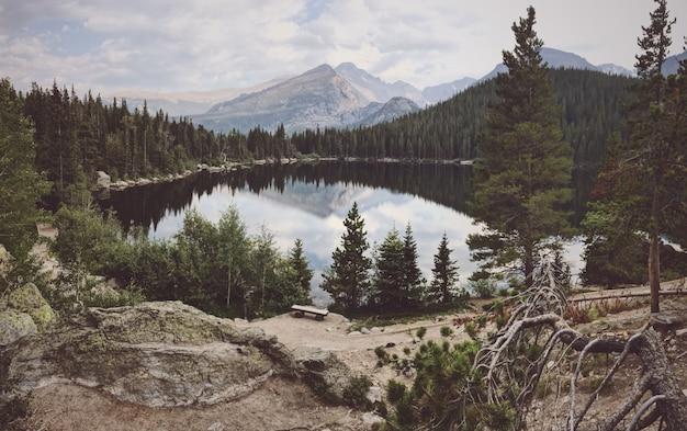 Grande plano de um grande lago cercado por árvores com uma montanha ao fundo
