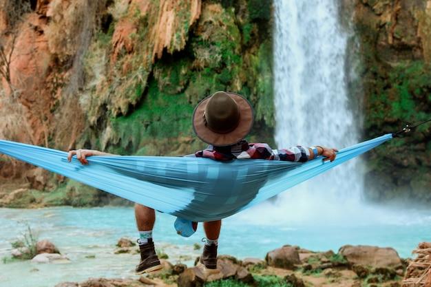 Grande plano de um homem deitado na rede ao lado de uma cachoeira que desce de uma colina