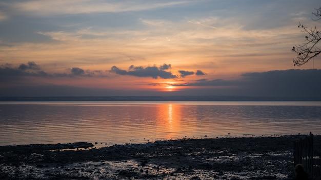 Grande plano de um mar sob um céu com nuvens durante o pôr do sol