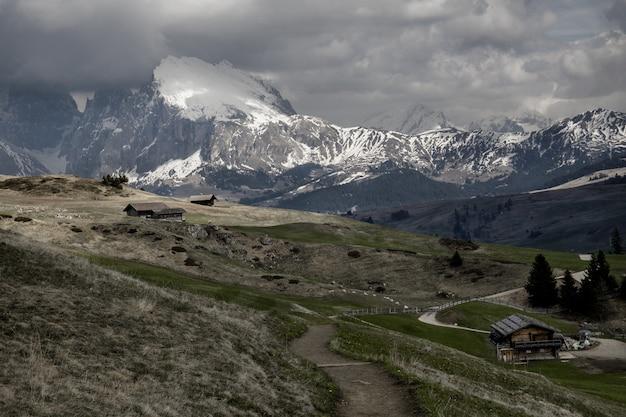 Grande plano de um pequenas cabines perto de montanhas cobertas de neve sob um céu nublado