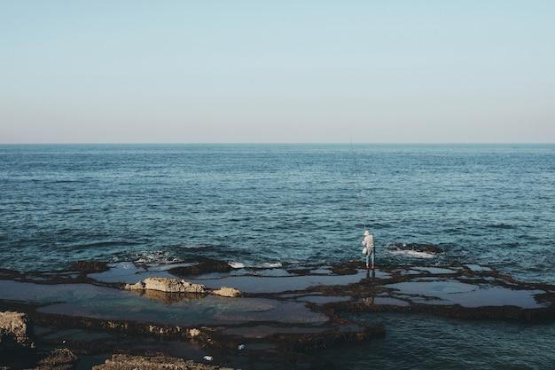 Grande plano de um pescador em pé na praia durante o dia