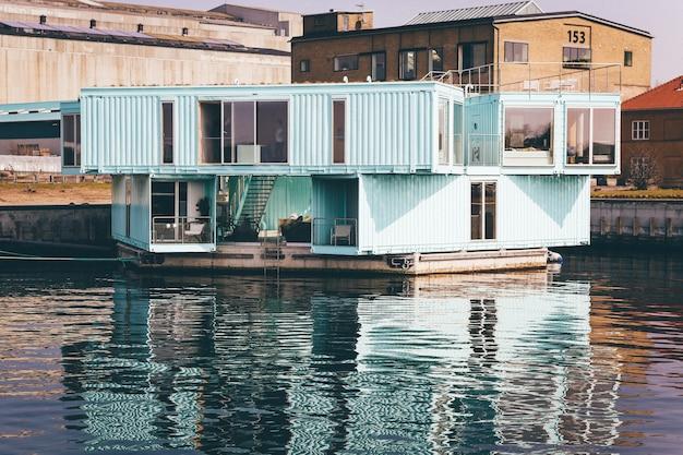 Grande plano de uma casa azul clara em uma doca no corpo de água