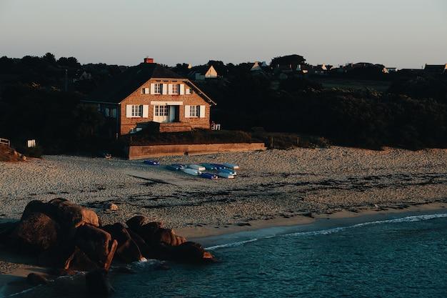 Grande plano de uma casa marrom em uma praia arenosa à beira-mar, rodeado de pedras e árvores