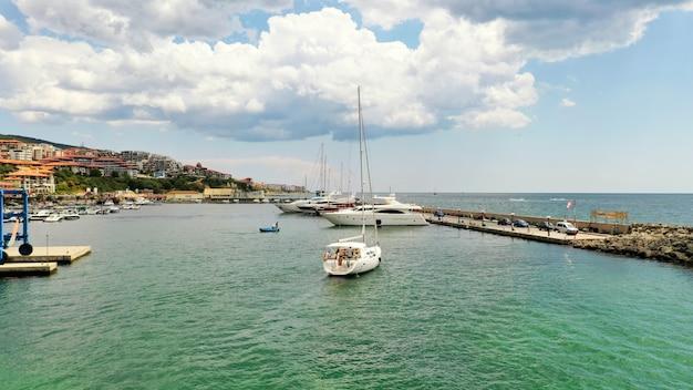 Grande plano de uma doca em uma cidade costeira com pessoas navegando em barcos perto da costa