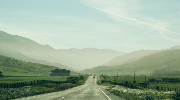 Grande plano de uma estrada no meio de um campo gramado com carros dirigindo e uma montanha florestada