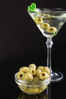 Grande plano de vidro com martini e azeitonas verdes