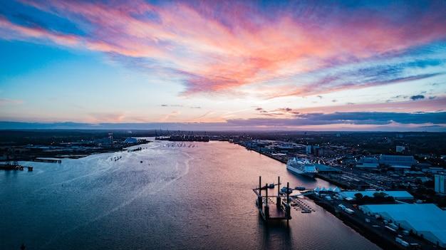 Grande plano distante de barcos flutuando no corpo d'água da cidade sob um céu rosado