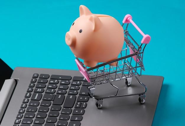 Grande plano do carrinho de compras com cofrinho no teclado do laptop