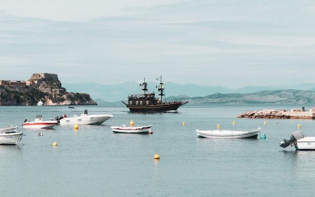 Grande plano dos barcos de pesca e barcos à vela em um lago