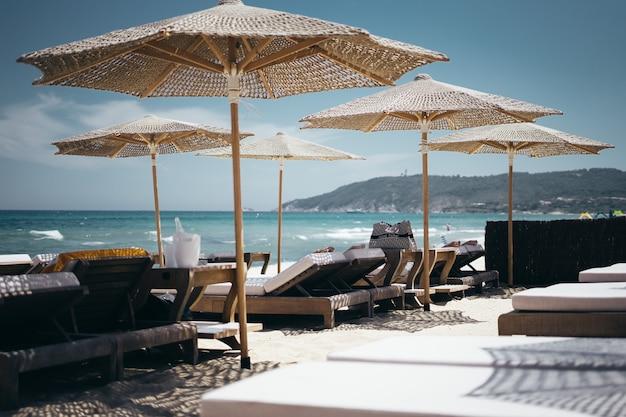 Grande plano seletivo de espreguiçadeiras de madeira marrons sob guarda-sóis na praia