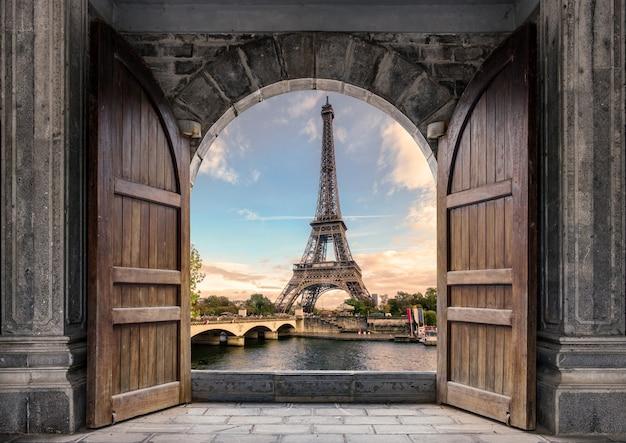 Grande porta de madeira aberta com a torre eiffel no rio sena ao pôr do sol em paris, frança